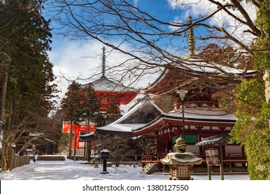 Toto Pagoda (East Tower) in Danjo Garan, Sanmaido Hall, Daiedo hall and Konpon Daito pagoda in the background, covered with snow on a sunny day, town of Koyasan, UNESCO World Heritage area, Japan.
