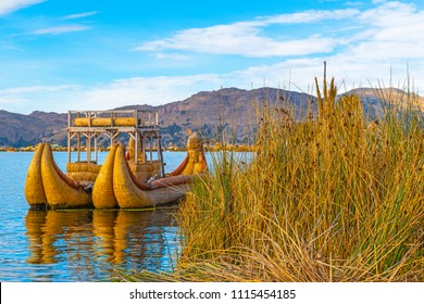 A totora reed boat by the Uros floating islands at sunrise with the Andes mountain range in the background near Puno, Peru, South America.