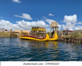 Totora yellow submarine boat near Uros floating islands,lake Titicaca, Peru. Bright scenic summer lake landscape on Titicaca near Puno. Traditional colorful reed boat.View on Peruvian side of Titikaka