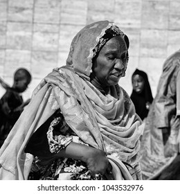 TOUBA, SENEGAL - APR 26, 2017: Unidentified Senegalese woman in colored traditional clothes walks in the Great Mosque of Touba, the home of the Mouride Brotherhood