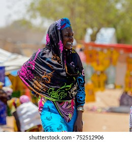 TOUBA, SENEGAL - APR 26, 2017: Unidentified Senegalese woman in traditional clothes walks at the local market neat Touba