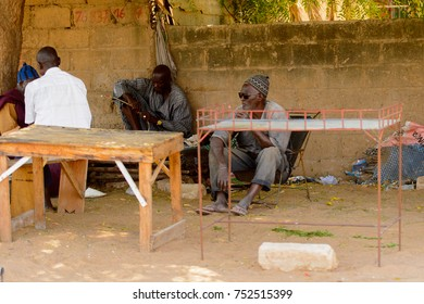 TOUBA, SENEGAL - APR 26, 2017: Unidentified Senegaleseman in sunglasses sits in a chair  in Touba, one of the major cities in Senegal