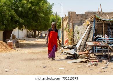 TOUBA, SENEGAL - APR 26, 2017: Unidentified Senegalese woman walks along the road in Touba, one of the major cities in Senegal