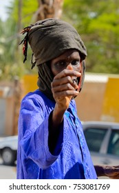 TOUBA, SENEGAL - APR 26, 2017: Unidentified Senegalese man in blue shirt and headscarf walks in Touba, one of the major cities in Senegal