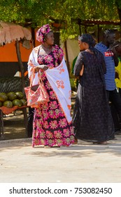 TOUBA, SENEGAL - APR 26, 2017: Unidentified Senegalese woman in traditional clothes walks at the market in Touba, one of the major cities in Senegal