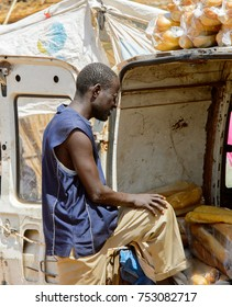TOUBA, SENEGAL - APR 26, 2017: Unidentified Senegalese man puts his foot on the car at the local market neat Touba