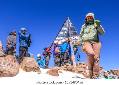 Toubkal/Morocco - 18/12/2018 : Tourists in the peak of Toubkal montain with a tourist woman walking back
