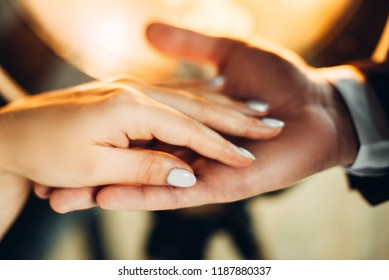 Touch of male and female hands against the background of warm light