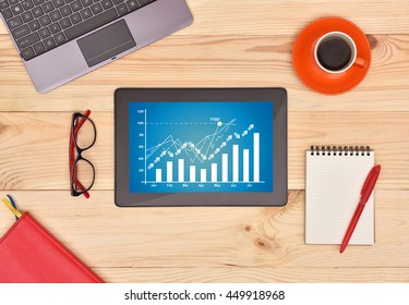 Touch pad with finance growth chart on screen and many objects on wooden desk.