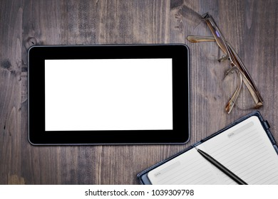 Touch screen device, notepad with pen and eyeglasses from above close-up