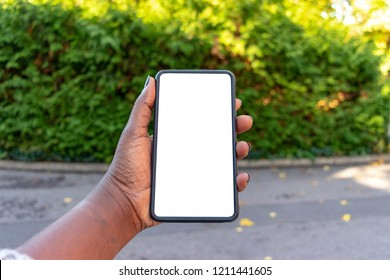 Touch screen mobile phone, in African woman's hand. Black Female holding smart phone on green outdoor background with blank copy space screen for your text message or information content