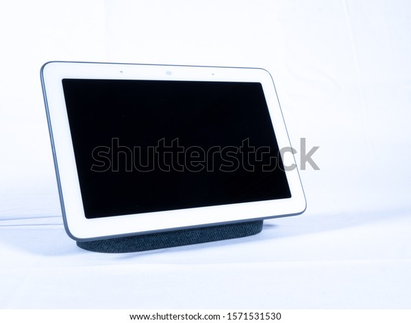 Touch screen smart home voice assistant speaker with blank screen on white background turned off
