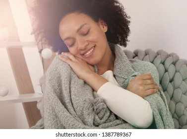 Touch of softness.Young woman enjoying softness of her cozy knitted sweater
