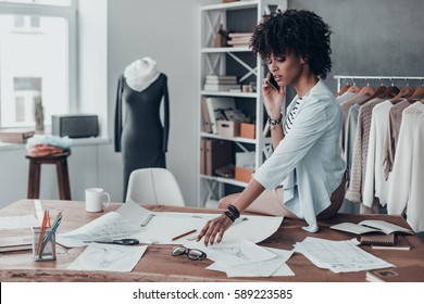 In touch with suppliers. Beautiful young African woman talking on smart phone while sitting on desk in her studio with clothes hanging in the background