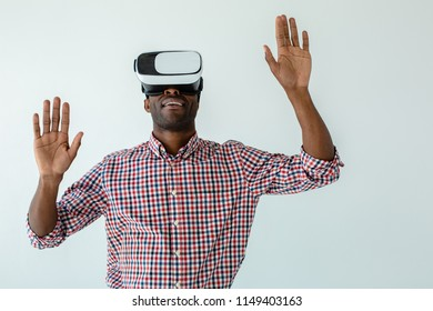 Touchable technologies. Waist up of cheerful smiling afro american man testing VR gadget while standing against white background