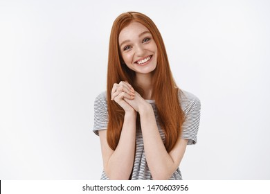 Touched charming cute happy carefree young ginger girlfriend blue eyes tilting head cheerfully cup hands together grateful receive hearwarming touching gesture look lovely camera, thanking friend