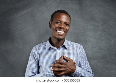 Touched and grateful African man smiling happily, holding hands on his chest to express his gratitude and thankfulness. Dark-skinned male looking pleased with some touching and hearth-piercing story