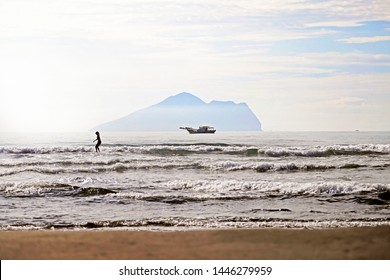 Toucheng Township, Yilan County/ Taiwan- May 31, 2019: A surfer surfing in the morning with small island background. The famous surfing spot in Taiwan.
