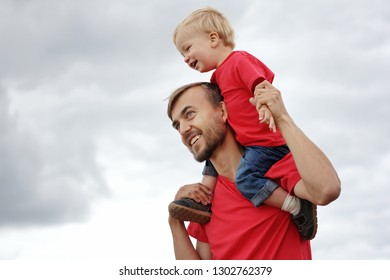 Touching family moments. Cute toddler boy sitting on his father's shoulders against the background of cloudy sky. They are smiling, laughing and looking happy. Parenthood or childhood concept.