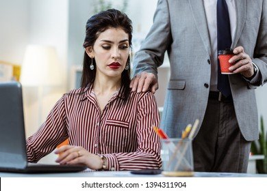 Touching female colleague. Resolute workmate in grey costume putting his hand on the shoulder of female colleague and confusing her