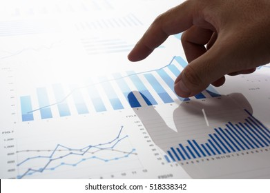 Touching growth chart. Reviewing accounting data. Many charts, graphs and hand. Reflection background.