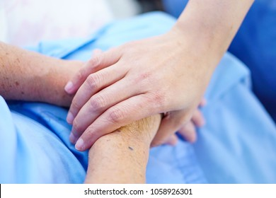 Touching hands Asian senior or elderly old lady woman patient with love, care, encourage and empathy at nursing hospital : healthy strong medical concept