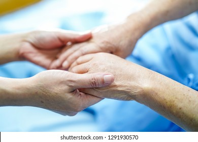 Touching hands Asian senior or elderly old lady woman patient with love, care, helping, encourage and empathy at nursing hospital ward : healthy strong medical concept