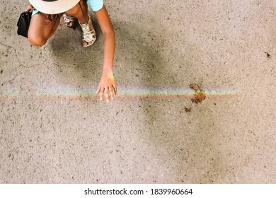 Touching the rainbow. A girl holding her hand under rainbow reflection on asphalt crossing rainbow with hand on Summer sunny day, view from above, photo with space for text.