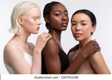 Touching shoulders. Three females with different skin touching shoulders of each other while posing