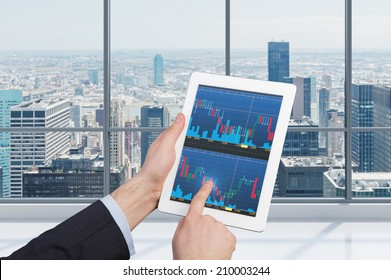 Touching stock market graph on a touch screen tablet. Trading on stock market concept.