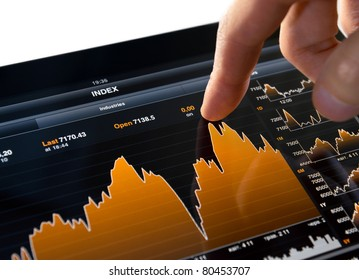 Touching stock market graph on a touch screen device. Trading on stock market concept. Closeup photo.