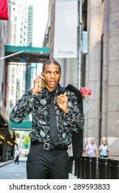 Tough African American businessman in New York. Wearing patterned shirt, tie, hand hooking jacket on shoulder, a young guy walking on street, talking on mobile phone, going to work. Instagram effect.