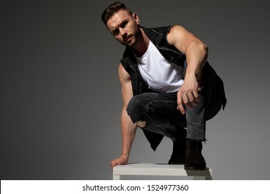 Tough casual man squatting and leaning on a chair while wearing a black jeans vest and jeans on gray studio background