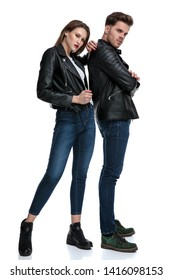 Tough couple posing while standing and looking to the camera, wearing leather jackets and jeans, he holding his arms folded at his chest while she is leaning on him and pulling her jacket