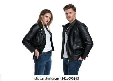 Tough couple standing with their hands in their back pockets and looking to the camera while wearing leather jackets and jeans on white studio background