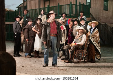 Tough cowboy with group of people in old west costumes