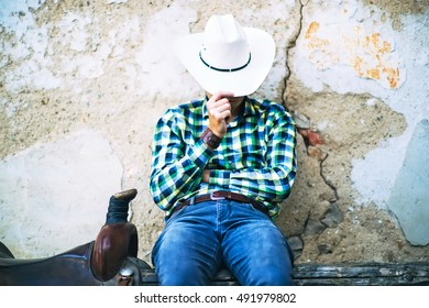 A tough cowboy guy sitting on a wooden fence. He holds his hat, wears jeans and shirt. A brown saddle is next to him. A typical american countryside photo.