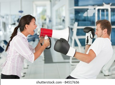 Tough female trainer yelling to a man with a megaphone while boxing