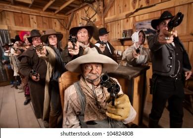 Tough group saloon customers aim their weapons straight ahead. Focus is on gun barrel.
