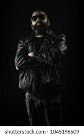 Tough guy in black leather jacket and sunglasses with arms crossed.