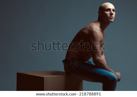 611105c3b4 Tough guy concept. Handsome bald muscular male model in blue jeans with  perfect muscular body