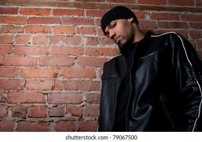 Tough guy dressed in black near a brick wall.