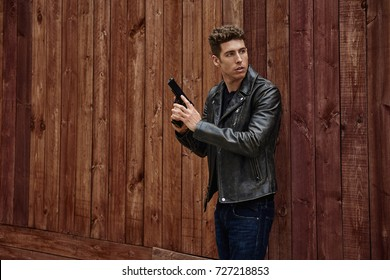 Tough guy in a leather jacket against a wood fence with a gun ready to go.