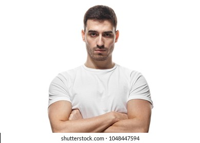 Tough guy standing with crossed arms isolated on white background. Serious young man portrait concept
