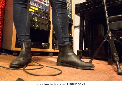 Tough looking singer in a rock band. Cool black boots and music gear in a studio.
