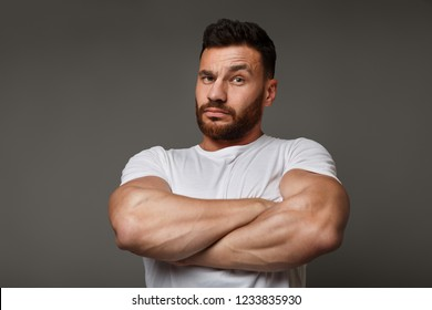 Tough macho with crossed arms looking at camera, gray studio background.