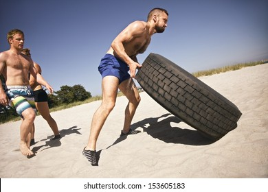 Tough male athlete flipping a truck tire. Young people doing  exercise on beach.