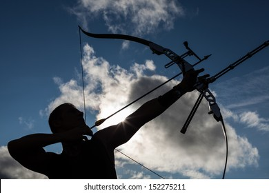 Tough man with bow and arrows, close up with cloudy sky at background