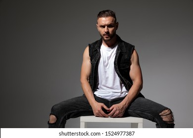 Tough man frowning and sitting with his legs apart while wearing a black jeans vest on gray studio background