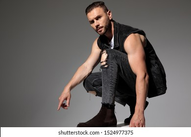 Tough man pointing down and squatting while wearing a black jeans vest and jeans on gray studio background